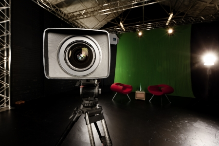 18080589 - close-up of a television camera lens in a green screen studio environment